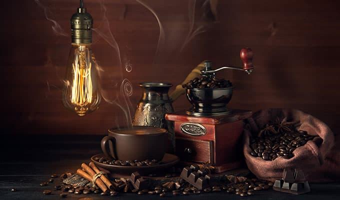 molinillo de café humeante con granos y taza de café