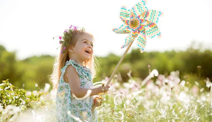 niña sonriendo en el campo con un molinillo de viento